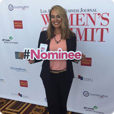 Recruiter at a Women's Summit holding a sign that reads '#Nominee'